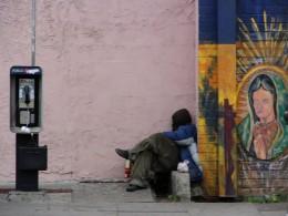 Homeless Man sleeping next to Virgin Mary